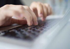 Close-up of human hands and keyboard